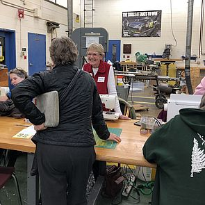 A sewing volunteer chats with a Repair Fair visitor